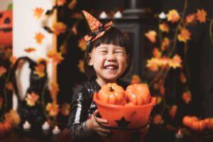 child holding a basket of pumpkins