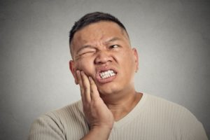 Pained man with hand on cheek experiencing dental emergency