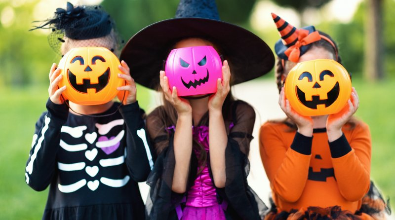 Children holding plastic pumpkins in their costumes