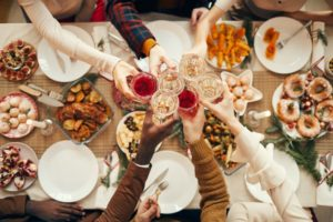 Hands clinking wine glasses together over a table of food